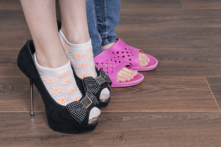Photo for Two children put on shoes, one of her mother shoes with heels, the other pink flip flops, close-up - Royalty Free Image