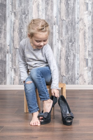 Foto de child wears her mother shoes on the leg while sitting on a small wooden chair - Imagen libre de derechos