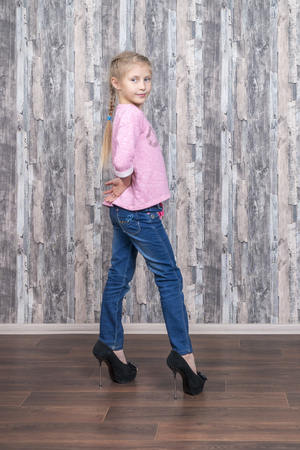 Photo for Young beautiful girl in jeans is fashionable in front of the camera in her mother shoes - Royalty Free Image
