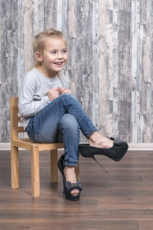 Photo for Cheerful little girl is sitting on a wooden chair and wearing her mother shoes - Royalty Free Image