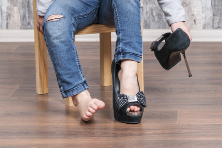Photo for baby puts on her mother high-heeled shoes sitting on a small chair - Royalty Free Image