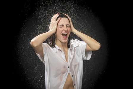 Photo for beautiful woman in a wet shirt clinging to the body screaming loudly clutching her head - Royalty Free Image