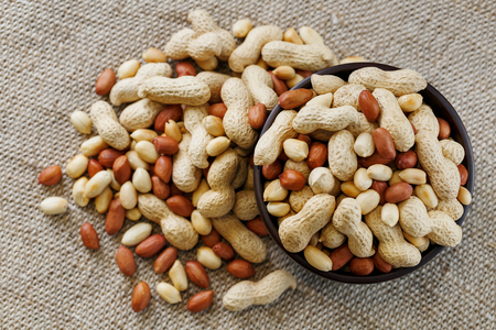 Peanuts in the shell and peeled close up in a cup. Background with peanuts. Roasted peanuts in the shell and peeled on a background of brown cloth in cups