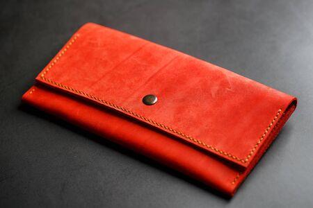 Photo pour Red leather wallet on a dark background top view. Close-up, purse details, rivet and firmware. Macro - image libre de droit