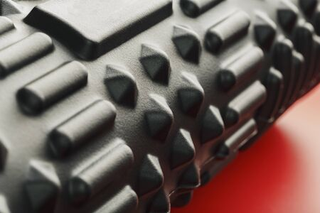 Photo pour Black lumpy foam massage roller on red background. For the mechanical and reflex effects on tissues and organs. Close-up, texture, element in macro - image libre de droit