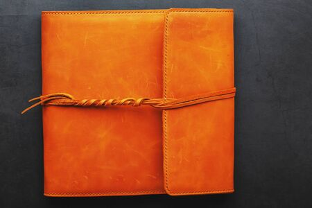 Foto de The album cover is made of brown genuine leather, handmade on a black background. Elements of a leather product close-up - Imagen libre de derechos