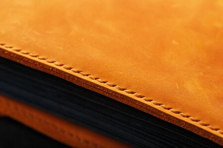 Foto de The leather cover of the album is made of brown handmade genuine leather on a black background. Elements of a leather product close-up. Craft, low contrast - Imagen libre de derechos