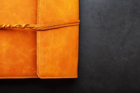 Foto de The leather cover of the album is made of brown handmade genuine leather on a black background. Elements of a leather product close-up. - Imagen libre de derechos