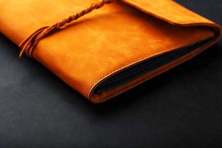 Foto de The album cover is made of brown genuine leather, handmade on a black background. Elements of a leather product close-up. - Imagen libre de derechos
