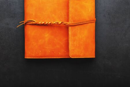 Foto de The album cover is made of brown genuine leather, handmade on a black background. Elements of a leather product close-up. Kraft - Imagen libre de derechos