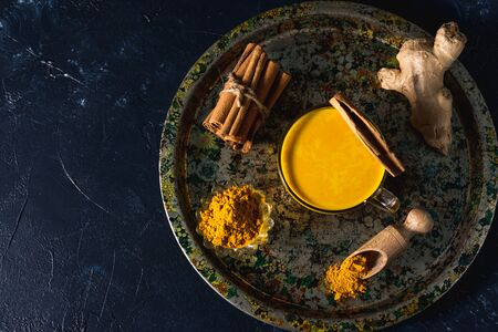 Photo for Golden turmeric milk on the dark background with spices cinnamon and ingredients - Royalty Free Image