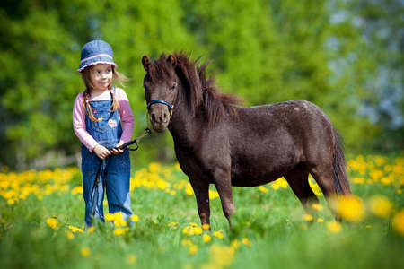 Photo pour Child and small horse in the field at spring. - image libre de droit