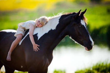 Portrait of child and a horse in filed