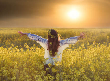 Photo pour Portrait of a young woman in a rapeseed field. Young joyful girl wearing traditional romanian blouse - image libre de droit