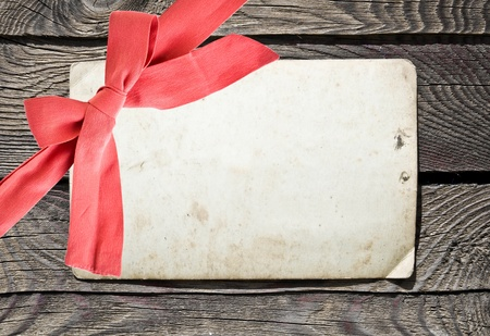 Grunge empty card and red bow on wood background