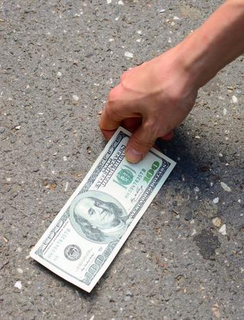 Hand picking money from street floor - Finding money on street concept