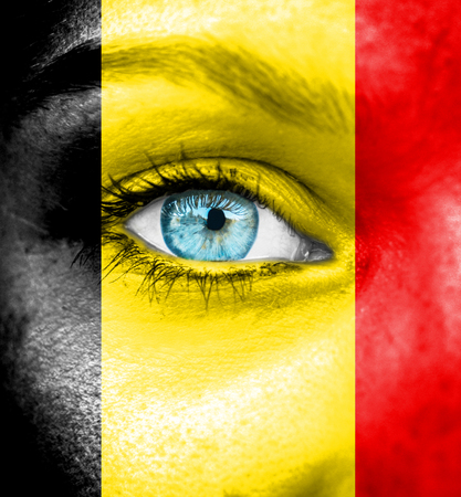 Woman face painted with flag of Belgium