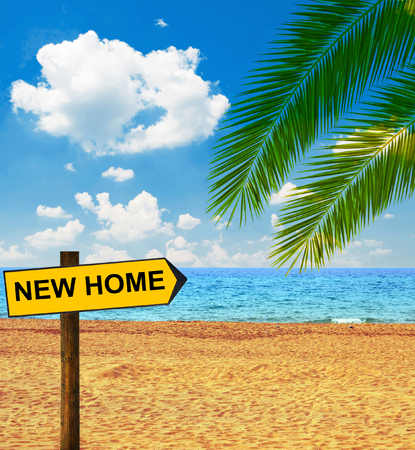 Tropical beach and direction board saying NEW HOME