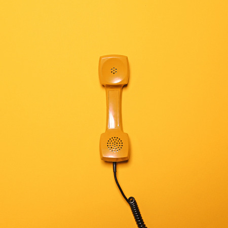 Photo pour Retro yellow telephone tube on yellow background - Flat lay - image libre de droit