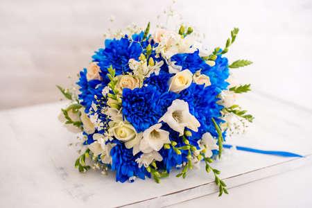 Foto de Beautiful modern wedding bouquet of blue chrysanthemum, freesia, roses and peony. on white wooden background. - Imagen libre de derechos