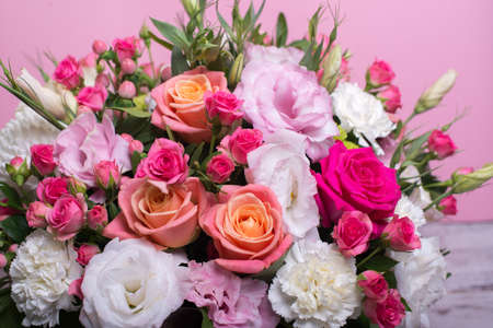Foto de beautiful floral arrangement in the box, pink and yellow rose, pink eustoma, green chrysanthemum, white carnation, pink dahlia on pink background with space for text - Imagen libre de derechos