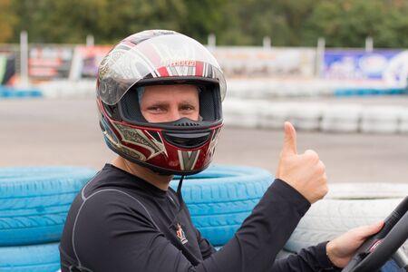 Photo pour active man in black competing on racing cars at kart circuit - image libre de droit