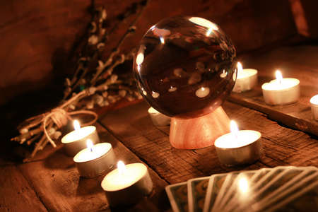 Foto de crystal ball for predicting the fate and supernatural action on the table from the old mahogany with candles and cards - Imagen libre de derechos