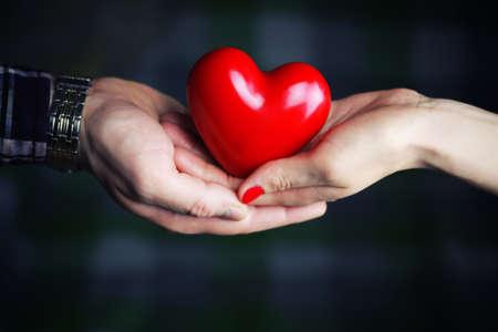Photo pour object red heart-shaped hands holding a young person - image libre de droit
