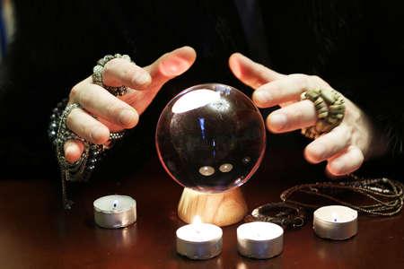 Photo pour sorcerer hands over a transparent crystal ball fortune-telling for the future - image libre de droit