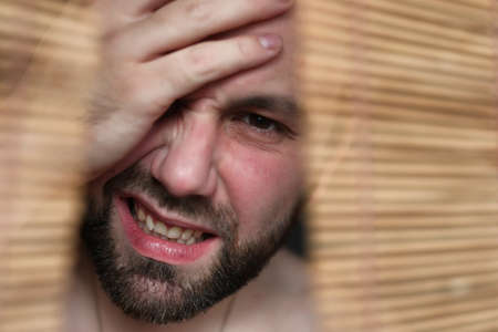 a man with a beard hides behind a wooden Roman Blinds and expresses his emotions