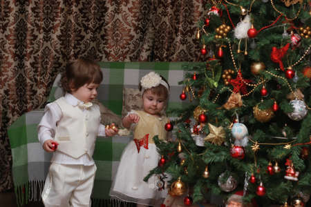 cute little kids on the floor in the interior of a child's room in the new year eve