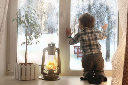 Photo for boy sitting on a white window sill and looks out the window - Royalty Free Image