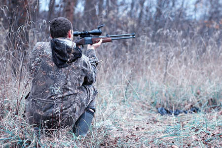 A man in camouflage and with a hunting rifle in a forest on a sp