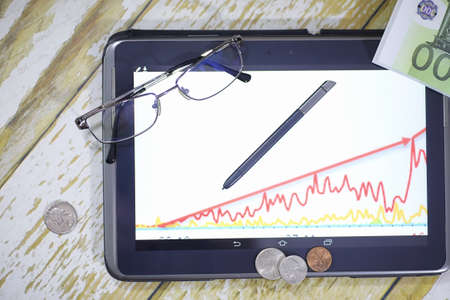 The graph of income growth. Electronic tablet with a graph of gr