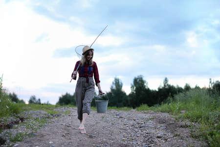 Photo pour Girl by the river with a fishing rod - image libre de droit