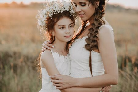 Photo pour mom and daughter hugging together in white dresses with braids and floral wreaths in summer - image libre de droit