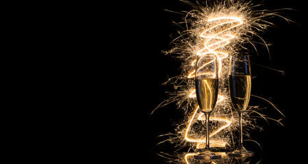 Foto de Two transparent glasses of champagne in Bengal lights on a black background - Imagen libre de derechos