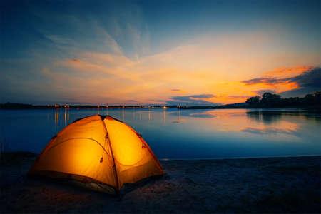 Photo pour Orange tent on the lake at dusk - image libre de droit