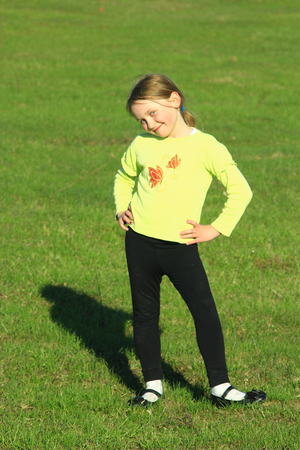little girl standing at in the majestic position on the green grass