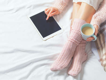 Woman using tablet at cozy home atmosphere on the bed. Young beautiful woman enjoying free time using technological device, holding a cup of cocoa or coffee. Soft light