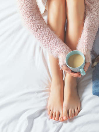 Photo for Woman relaxing at cozy home atmosphere on the bed. Young woman with beautiful skin and nails with cup of cocoa or coffee in her hands enjoying comfort. Soft light and comfy beauty natural lifestyle. - Royalty Free Image