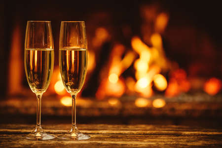 Foto de Two glasses of sparkling champagne in front of warm fireplace. Cozy relaxed magical atmosphere in a chalet house by the fireside. Snug holiday concept. Beautiful background with shimmering wine. - Imagen libre de derechos