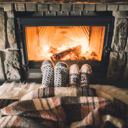 Couple sitting under the blanket, relaxes by warm fire and warming up their feet in woolen socks.