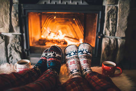 Photo for Feet in woollen socks by the Christmas fireplace. Couple sitting under the blanket, relaxes by warm fire and warming up their feet in woollen socks. Winter and Christmas holidays concept. - Royalty Free Image