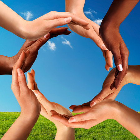 Photo pour Conceptual peace and cultural diversity symbol of multiracial hands making a circle together on blue sky and green grass background. - image libre de droit