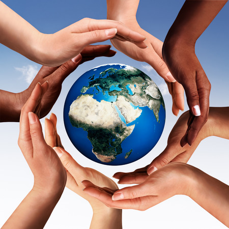 Foto de Conceptual peace and cultural diversity symbol of multiracial hands making a circle together around the world the Earth globe on blue sky background - Imagen libre de derechos