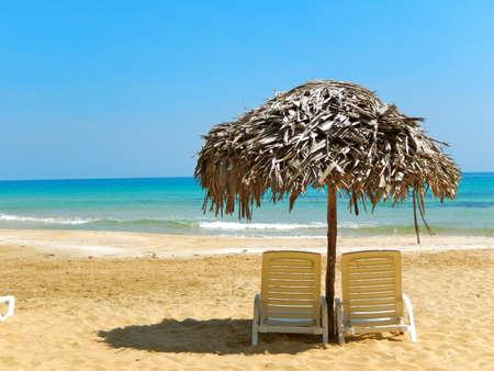 Beach Chairs Under Grass Umbrella