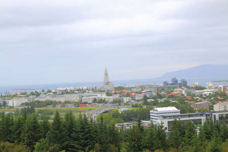 Wide-angle aerial view of Reykjavik, Iceland with harbor and skyline mountains.