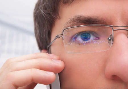 Financier in glasses looking at monitor.
