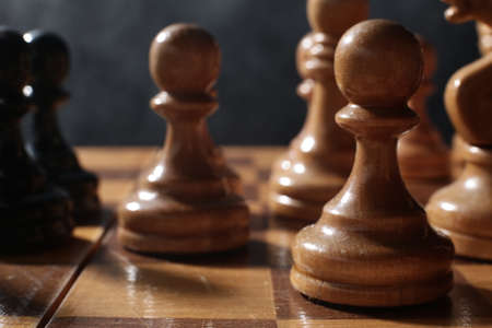 Photo pour Wooden chess is a board game. Chess pieces on a dark background - image libre de droit
